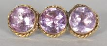 A YELLOW GOLD BROOCH, set with three large AMETHYSTS. <br>