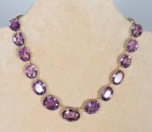 A SUPERB ANTIQUE GRADUATED AMETHYST AND GOLD NECKLACE, set with seventeen oval stones. <br>