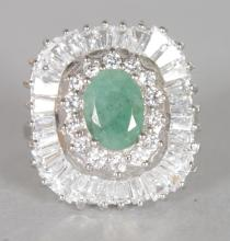 A LARGE EMERALD AND BRILLIANT SET CLUSTER RING, set in silver. <br>