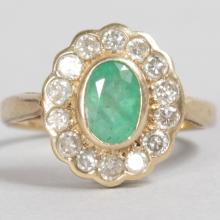 A 9CT YELLOW GOLD, EMERALD AND DIAMOND OVAL CLUSTER RING.