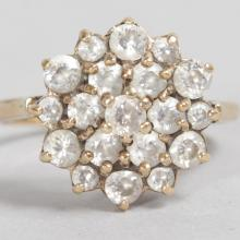 A 9CT YELLOW GOLD DIAMOND FLOWER HEAD CLUSTER RING.