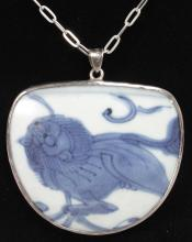 A SILVER MOUNTED MING BLUE AND WHITE PENDANT on a chain.
