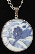 A MING BLUE AND WHITE PORCELAIN AND SILVER MOUNTED PENDANT on a chain.