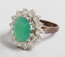 A GOOD LARGE EMERALD AND DIAMOND OVAL CLUSTER RING with large central emerald surrounded by fourteen diamonds in 9ct yellow gold.