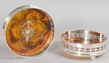 A PAIR OF SILVER PLATE AND FAUX TORTOISESHELL CIRCULAR WINE COASTERS, supported on four bun feet.  4.5ins diameter.