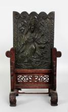 A CHINESE BRONZE TABLE SCREEN, possibly Ming Dynasty, together with a fitted wood stand, the front of the bronze cast in relief with the Immortal Lan Ts'ai Ho bearing a basket of flowers, the whole with good unpolished patination, the screen as a whole 13.5in(34.2cm) high & 8.4in(21.3cm) wide at widest point, the bronze plaque itself 8.5in(21.5cm) high & 6.1in(15.4cm) wide. Bought in Rangoon 1928.