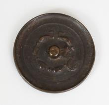 ANOTHER SMALL CHINESE BRONZE MIRROR, possibly early, the indistinct cast decoration including a circular seal, 2.8in(7.3cm) diameter. Bought in Rangoon 1931.