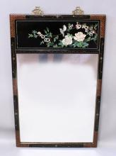 A 20TH CENTURY CHINESE LACQUERED WOOD MIRROR, decorated with a shallow carved and lacquered panel of two birds perched on a blossoming bough above a mirrorinset, 26in(66cm) wide & 41.75in(106cm) high.
