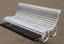 A GOOD WROUGHT IRON AND WOODEN SLATTED WHITE PAINTED GARDEN BENCH of scrolling design.