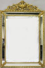 A SUPERB 19TH CENTURY FRENCH ORMOLU FRAMED UPRIGHT MIRROR with urn surmount, pierced scrolls and bevelled glass. <br>5ft high, 3ft wide.