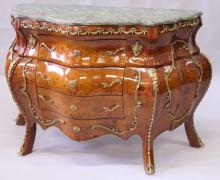 A LOUIS XVI STYLE MARBLE TOP WALNUT COMMODE, of bombe form, with ormolu mounts, the three long drawers supported on cabriole legs. <br>3ft 5ins wide x 2ft 7ins high x 1ft 4ins deep.