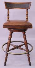 A MAHOGANY BAR STOOL, with upholstered swivel seat, on turned and reeded legs with brass footrest. <br>3ft 6ins high.