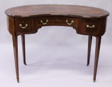 AN EDWARDIAN MAHOGANY KIDNEY SHAPE DESK, with leather inset top, central frieze drawer flanked by a pair of deep drawers, all fitted with Hobbs locks, supported on tapering square legs with brass castors. <br>3ft 6ins wide x 1ft 8ins deep x 2ft 5ins high.