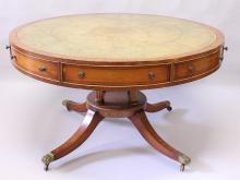 A GOOD SHERATON REVIVAL SATINWOOD DRUM TABLE, with gilt tooled leather inset top, foliate painted borders above four real and four dummy drawers, supported on four turned and fluted columns, a circular base with painted decoration and four sabre legs with brass castors. <br>4ft 4ins diameter x 2ft 5ins high.
