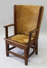 A GOOD CHILD'S ORKNEY CHAIR, of typical form, with oak frame and drop-in rush seat on stretchered tapering legs. <br>2ft 8ins high.