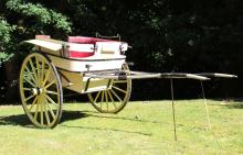 A LATE 19TH CENTURY GOVERNESS CART, with a pair of large wooden spoked wheels, with rubber tyres, wrought iron leaf springs, cream, yellow and red painted body work. <br>11ft 0ins long x 6ft 0ins wide.