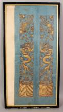 A PAIR OF 19TH/20TH CENTURY CHINESE EMBROIDERED SILK SLEEVE PANELS, in a single frame, each embroidered in gilt thread with a dragon and a phoenix above waves, the frame 25.25in x 13.3in.