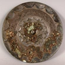 A CHINESE SILVERED BRONZE CIRCULAR MIRROR, possibly Tang Dynasty, the top surface with formal designs and pronounced patinated encrustations, 5.4in diameter.
