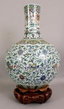 A LARGE GOOD QUALITY CHINESE DOUCAI PORCELAIN BOTTLE VASE, together with a fitted wood stand, the sides decorated with formal scrolling lotus and ribboned emblems, the base with a Qianlong seal mark, the vase itself 14in wide at widest point & 21.4in high.