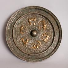 A GOOD GILDED & SILVERED CHINESE TANG DYNASTY BRONZE MIRROR, of circular form, decorated to its centre in relief with alternating gilded phoenix and hounds encircling a domed knop, with a border of character inscriptions, the whole with good patination, 8.1in diameter.