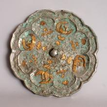 ANOTHER GOOD GILDED & SILVERED CHINESE TANG DYNASTY BRONZE MIRROR, of barbed octofoil form, decorated to its centre in relief with gilded phoenix amidst scrolling foliage encircling a domed knop, within a border of vine to the rim, the whole with good green patination, 8.6in diameter.
