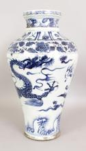 A LARGE CHINESE YUAN STYLE BLUE & WHITE PORCELAIN DRAGON VASE, decorated with a dragon pursuing a flaming pearl above waves, the base unglazed, 18.6in high.