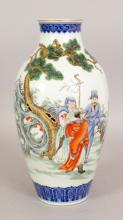 A GOOD QUALITY CHINESE FAMILLE ROSE PORCELAIN VASE, decorated with a group of Immortals conversing in a garden setting of rockwork and overhanging pine, the base with a Qianlong seal mark, 10.8in high.