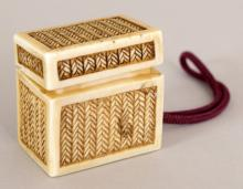 AN UNUSUAL SIGNED JAPANESE MEIJI PERIOD IVORY CORD NETSUKE OF A REED WOVEN RECTANGULAR BOX & COVER, the interior containing the moveable head of a one eyed demon, the base with an engraved signature, 1.25in x 0.8in x 1.25in high.