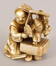 A GOOD QUALITY SIGNED JAPANESE MEIJI PERIOD STAINED IVORY OKIMONO OF A PUPPETEER, kneeling and holding his puppet before him, the base with two signatures, one engraved, the other on an inlaid red lacquer reserve, 1.5in high.
