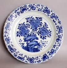 A GOOD 17TH/18TH CENTURY CHINESE KANGXI MARK & PERIOD BLUE & WHITE PORCELAIN DISH, together with a later fitted box, the dish painted to its centre with plum blossom and rockwork within a floral border to the barbed and shaped rim, the base with a six-character Kangxi mark, 14.2in diameter.