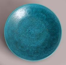 A GOOD 18TH CHINESE TURQUOISE GLAZED PORCELAIN DISH, together with a later fitted box, incised under the glaze with a design of scrolling peony and leafage, 10.3in diameter.