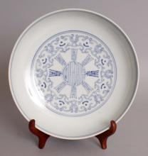 A GOOD 18TH CENTURY CHINESE QIANLONG MARK & PERIOD BLUE & WHITE PORCELAIN SAUCER DISH, together with a later fitted box & wood display stand, the dish painted to its centre with a central Shou medallion encircled by smaller Shou characters within a design of interlocking C scrolls, the exterior rim with stylised Shou characters and similar C scrolls, the base with a Qianlong seal mark, 8.1in diameter.