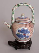 A GOOD 17TH CENTURY CHINESE FAMILLE VERTE PORCELAIN EWER & COVER, possibly Tianqi period, together with a good quality fitted carved hardwood stand and a later fitted box, also a typed receipt dated 1972, the ewer with overhead handle, the sides painted with circular panels of seasonal foliage reserved on a variety of trellis grounds, the ewer itself 5.75in long including handle & 7in high to top of handle.