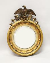 A 19TH CENTURY GILT FRAMED CONVEX MIRROR, with carved eagle cresting, ball finial applied frame. <br>2ft high