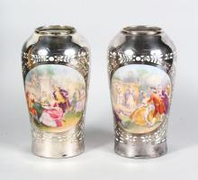 A GOOD PAIR OF FRENCH SILVER OVERLAY VASES, painted with reverse panels of scenes with gallant and lady in a garden setting. <br>9in high in a fitted leather case retailed by TAMAIL A RAHEEM