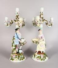 A GOOD PAIR OF LARGE CONTINENTAL DRESDEN DESIGN FOUR LIGHT CANDLE STICKS, each enameled with flowers, the stem with a gallant and young lady carrying baskets <br>21in high