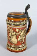 A GOOD METTLACH POTTERY TANKARD, etched with a band of revelling figures Pattern No: 2057 <br>7in high