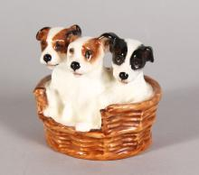A ROYAL DOULTON GROUP OF THREE TERRIER PUPPIES, in a basket H.N.2588, withdrawn 1985