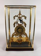 A LARGE SKELETON CLOCK, the brass dial engraved with signs from the zodiac, in a glass case. <br>2ft 0ins high.