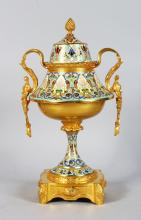 A SUPERB 19TH CENTURY FRENCH GILT ORMOLU CHAMPLEVE ENAMEL TWO HANDLED URN AND COVER, modelled as a cup with pineapple finial, loop handles with female masks and with high quality Champleve enamel decoration. <br>13.5in high