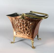 AN EDWARDIAN COPPER COAL SCUTTLE, with floral repousse panels, swing handle on claw feet