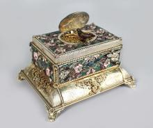 A SUPERB 19TH CENTURY GERMAN SILVER AND ENAMEL TABLE SINGING BIRD MUSICAL BOX, with oval enamel flip up top revealing a singing bird, small sliding drawer to the base, the siver gilt case engraved and with enamel decoration (in working order with key) <br>5.25in long x 4in wide 3in high