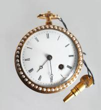 A GOLD AND ENAMEL FOB WATCH, with white enamel dial, Roman numerals, the bezels set with seed pearls, the back engine turned and green enamel decorated. <br>1.5ins diameter.