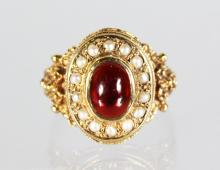 A 9ct GOLD RING SET WITH CABOUCHON GARNET AND SEED PEARL
