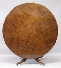 A GOOD 19TH CENTURY BURR WALNUT CIRCULAR TILT TOP BREAKFAST TABLE, with turned and carved column support on four out-swept legs with brass castors. <br>4ft 6ins diameter x 2ft 4ins high.