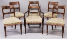 A SET OF SIX WILLIAM IV MAHOGANY DINING CHAIRS, one with arms, panelled top rail, overstuffed seats on turned legs.