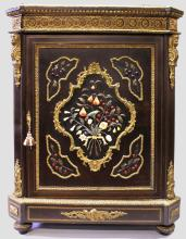 A SUPERB VICTORIAN EBONY AND PIETRA DURA CABINET with rich ormolu mounts, with patria female masks, the doors inset with coloured jades and marble in the Pietra Dura style, with birds, fruit and flowers, the door opening to reveal a series of shelves and supported on turned bun feet. <br>4ft 4ins high, 3ft 3ins wide, 1ft 7ins deep.
