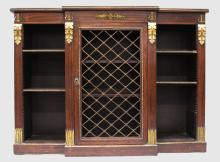 A GOOD REGENCY ROSEWOOD STANDING LOW BREAKFRONT BOOKCASE, the front with grilled door flanked by open shelves with acanthus ormolu mounts, and supported on a platform base. <br>2ft 10ins high, 3ft 10ins long, 1ft 1ins deep.