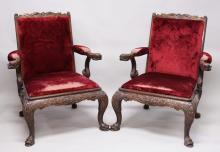 A GOOD PAIR OF ANGLO INDIAN CARVED OPEN ARMCHAIRS with carved dragon arms, padded back and seats, supported on carved cabriole legs.