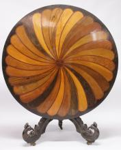 A SUPERB 19TH CENTURY ANGLO INDIAN (CEYLON) CIRCULAR TRIPOD TABLE, 3ft 7ins diameter, the top with swirl decoration in specimen woods, supported on a turned column with three curving legs with castors. <br>Note: A similar table sold at Christies 2010 for £30,000.